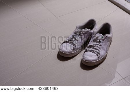 Used White Sneakers In Weak Light With Copy Space