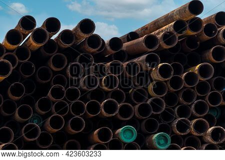 Pile Of Old Rusty Round Metal Industrial Pipe. Steel Pipe Stack At Warehouse Of Factory. Industrial