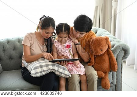 Parents And A Kid Child Look At A Laptop At Their Leisure In A Weekend At Comfortable Home.