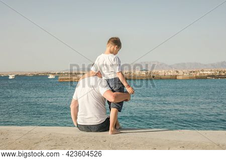 Father And  Son  Spending Time Together Sea Vacation. Little Boy And Dad Sitting On Beach And Looks