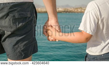 Father's Day. Father And Son. Little Boy Holding The Hand Of His Father. Young Man, Little Boy Walki