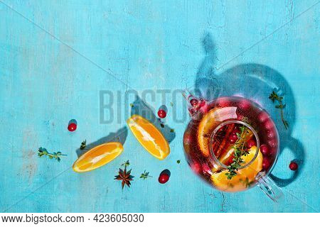 Immunity Boosting Drink. Tea With Cranberries, Orange And In Glass Teapot On Turquoise Table