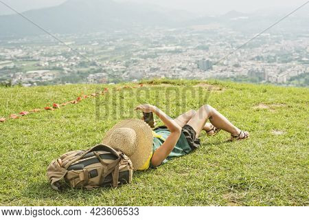 Asian woman lie on grassland and using cellphone