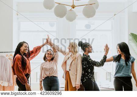 Businesswomen giving a high five to team