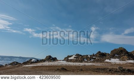 Winter Landscape. There Is Snow And Dry Grass In The Valley. Against The Background Of The Blue Sky,