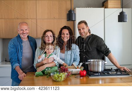 Happy Multigeneration Family Indoors Cooking At Home, Looking At Camera.
