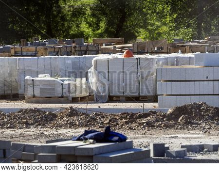 There Are Many Building Materials On The Construction Site. The Curbstone Is Stacked In Piles. The P