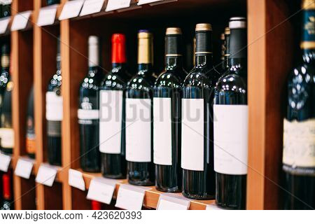Showcase With Wine Bottles At Wine Store. Wall With Alcoholic Drinks Wine Bottles On Shelves.