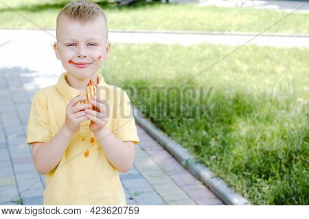 A Child Eating A French Hot-dog And Stains His Clothes With A Ketchup Stain.the Concept Of Cleaning