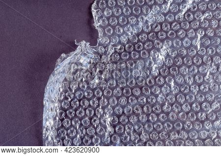 Protective Bubble Wrap On Colored Background. Texture Of Plastic Wrap With Carelessly Torn Edge. Top