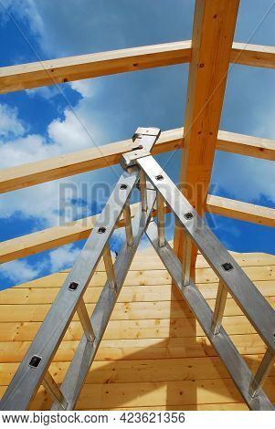 A Ladder In A Partially Constructed Wood (fir) Block House, A Pre-cut Wooden House Which Is Assemble