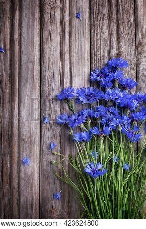 Blue Cornflowers On Rustic Wooden Board Top View.