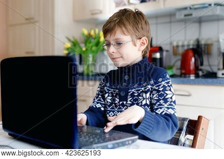 Kid Boy With Glasses Learning At Home On Laptop For School. Adorable Child Making Homework And Using