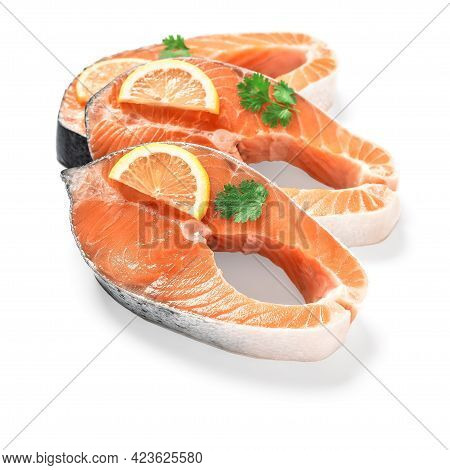 Raw Salmon Steaks Isolated On White Background. Slices Of Fresh Red Fish With Lemon And Greens. Sele