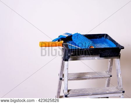 Cuvette For Rollers With A Roller And Brush Filled With Blue Paint Stands On A Stepladder