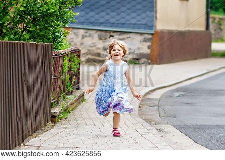 Happy Little Toddler Girl Running On Street In The City, Outdoors. Funny Preschool Child Hild Having