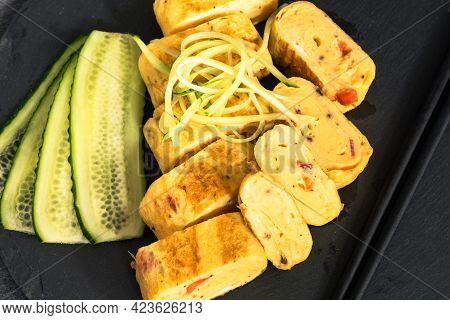 Traditional Japanese Tamagoyaki Omelet. Pieces Of Tamago-yaki On A Slate Board With Sliced Cucumbers
