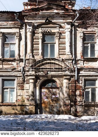 Saratov, Russia, March 30, 2019 - Facade Of An Old Dilapidated Mansion With An Arched Door And False