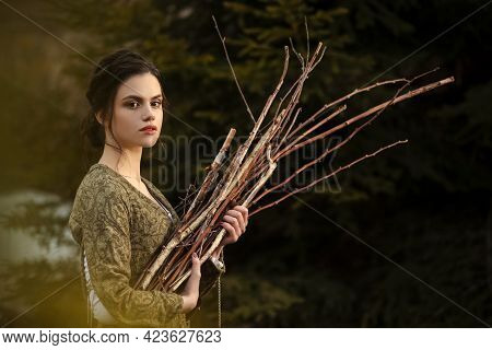 Young Brunette Caucasian Housewife Posing In Spring Forest With Bunch Of Firewoods In Hands Outdoors