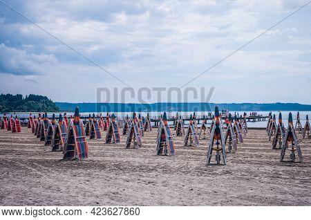 Closed Parasols Umbrellas On The Beach, No Tourists