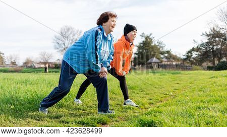 Healthy Lifestyle Concept. Happy Grandmother And Granddaughter Doing Sports Together It The Park. Ol