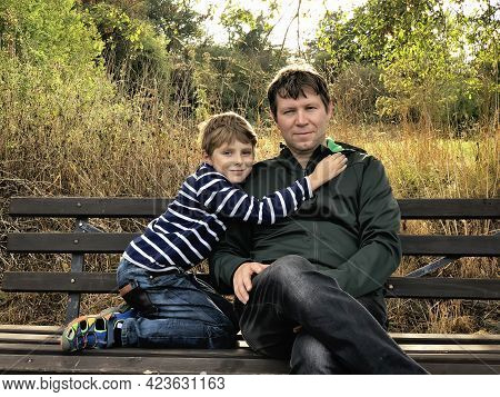 Cute School Kid Boy And Father Together Outdoors. Happy Child And Dad, Young Man Sitting On Bench. F