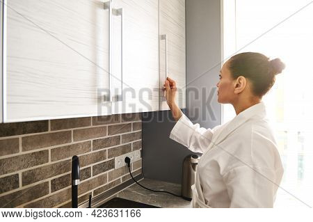 Side View Of A Young Woman In A White Waffle Bathrobe Opening A Cupboard In The Kitchen. Morning Rou