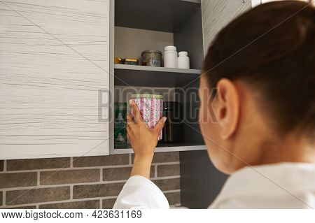 Young Woman In A White Waffle Dressing Gown Opens A Cupboard In The Kitchen And Takes Out A Jar Of C
