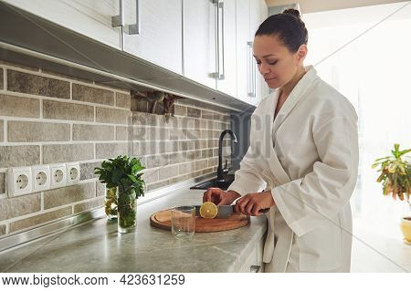 Charming Woman In White Bathrobe Standing In The Home Kitchen And Cutting Lemon For Preparing Lemon