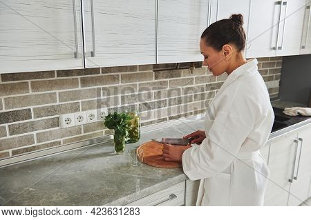 Young Beautiful Woman In White Waffle Bathrobe Cutting Lemon On A Wooden Board To Prepare Lemon Mint