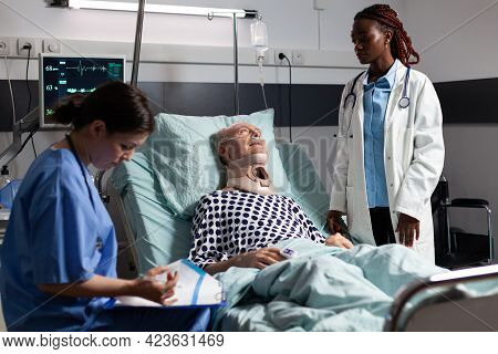 Injured Senior Man With Neck Brace Laying In Bed Suffering After Accident, Discussing With African D