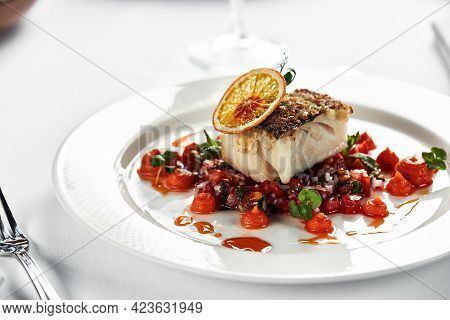 Black Cod Fillet On A Vegetable Stew, Festive Serving On A White Grater On A Table With White Tablec