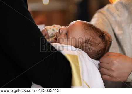 Man Holding Adorable Baby In Church During Baptism Ceremony, Closeup