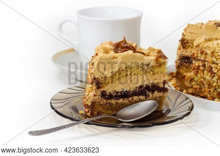 Piece Of Layered Sponge Cake, Decorated With Butter Cream, Caramelized Condensed Milk, Crumbled Nuts