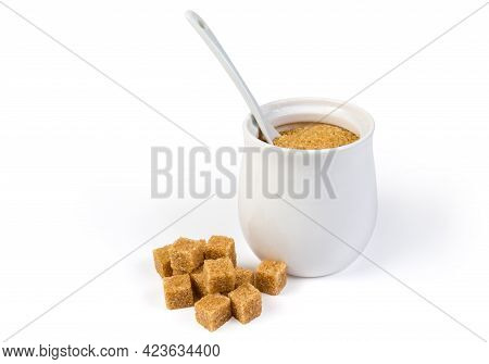 Natural Unrefined Brown Granulated Sugar In White Sugar-bowl With Spoon And Cubes Of Brown Sugar Sca