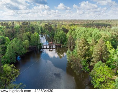 Scenic Narrow Long Lake With Shores Overgrown With Different Trees And Shrubs And Wooden Footbridge