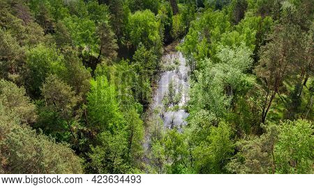 Small Narrow Overgrown Lake Among The Surrounding Forested Hills In Early Summer, Aerial View