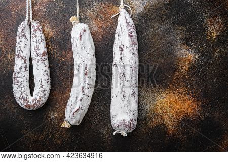 Dry Cured Chorizo And Fuet Salami Sausages Hanging On Dark Background.