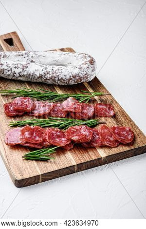 Fuet Whole And Sliced Cuts, Spanish Dry Cured Sausage On White Surface.