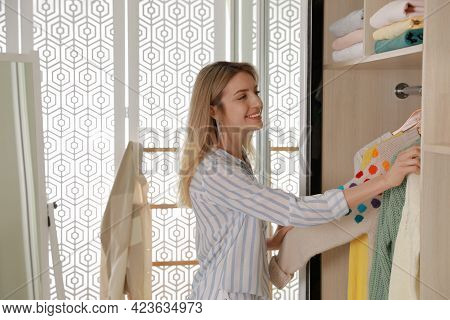 Young Woman Putting Clothes Into Wardrobe At Home