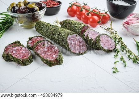 Traditianal Fuet Sausage In Herbs With Ingredients On White Textured Background.