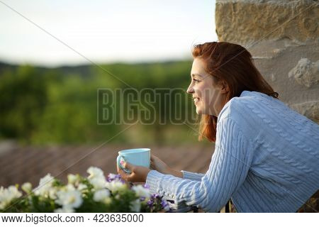 Side View Portrait Of A Happy Woman Contemplating From Balcony With Coffee Cup
