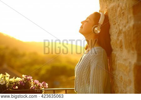 Side View Portrait Of A Relaxed Woman Resting Standing In A Balcony Listening To Music With Wireless