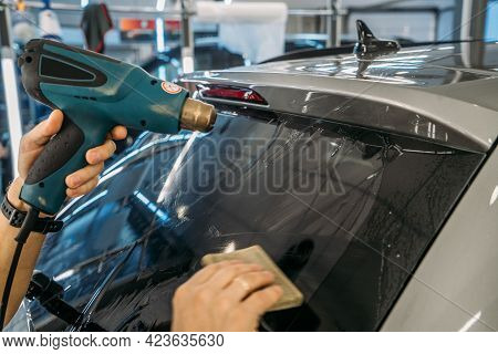 Professional Detailer Warms Up Tint Film With Industrial Dryer To Apply Tinting On Car Glass, Close