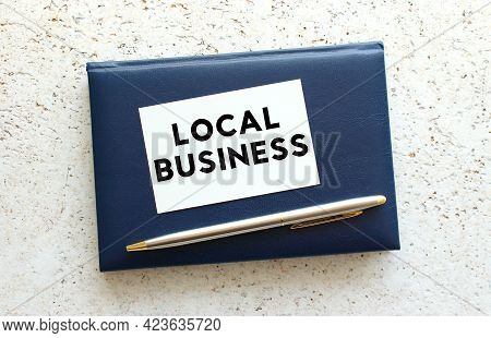 Text Local Business On A Business Card Lying On A Blue Notebook Next To The Pen. Business Concept.