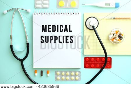 A Notebook With The Text Medical Supplies Is Neatly Folded Among The Pills, A Stethoscope, And A Yel