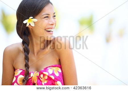 Beach woman happy looking to side laughing having fun smiling joyful and elated wearing sarong and flower on Hawaii. Multiracial Asian / Caucasian girl.