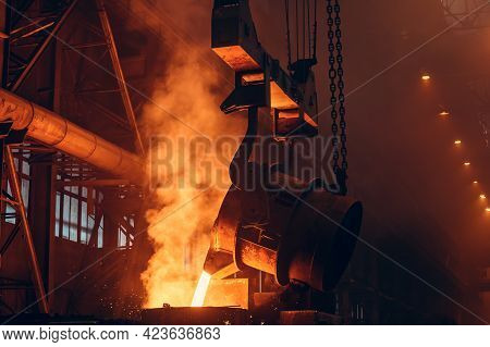 Foundry. Metal Cast Process. Molten Iron Pouring With Sparks And Smoke In Metallurgical Plant.