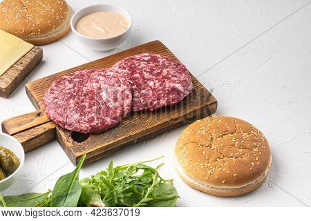 Homemade Hamburger. Raw Beef Patties, Sesame Buns With Other Ingredients Set, On White Stone  Backgr