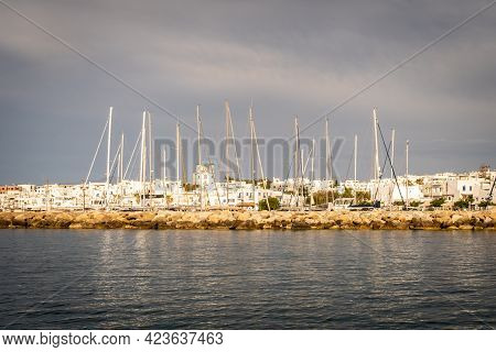 Row Of White Sailboats Docked In Naoussa Coastal Village Port Paros Island During Golden Hour With T